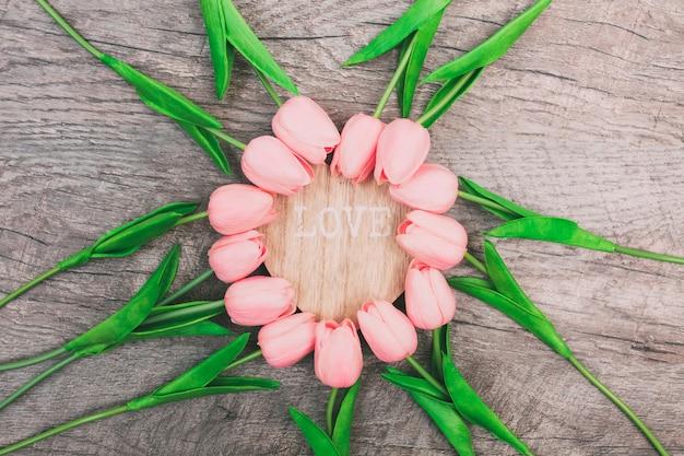 Zachte roze tulpen, neergelegd in de vorm van een cirkel, op een houten achtergrond.