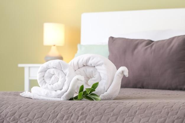 Zachte schone handdoeken opgerold in de vorm van een slak op bed