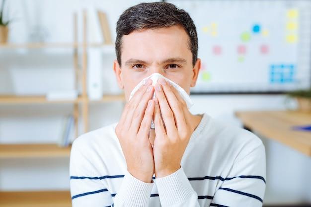 Zachte servet. zieke mannelijke persoon draagt gestreepte trui en hand in hand samen terwijl hij zich slecht voelt