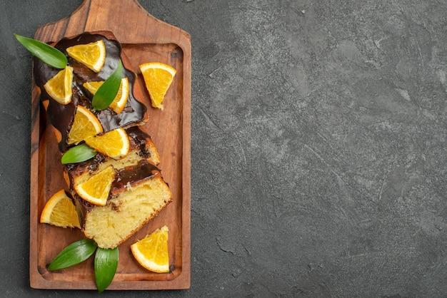 Zachte taarten geheel en gesneden sinaasappels met bladeren op donkere tafel