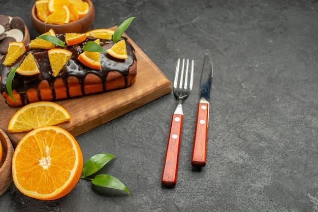 Zachte taarten op houten snijplank en gesneden sinaasappelen met bladeren, koekjes, vork en mes