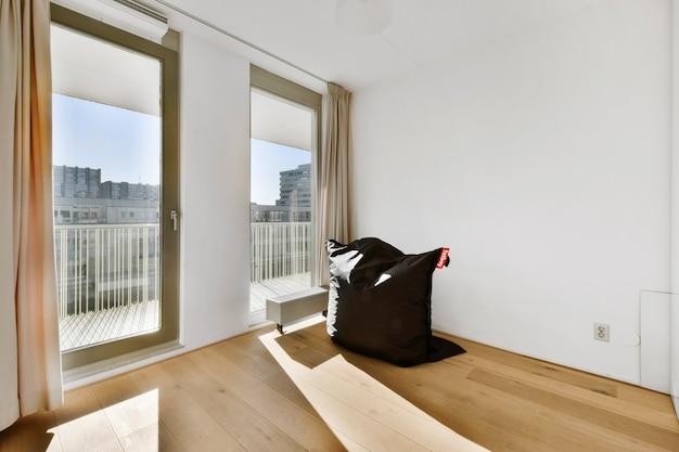 Zachte vierkante zitzak in de buurt van ramen in lichte, stijlvolle kamer van moderne flat