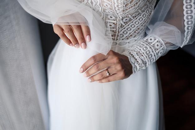Zachte vrouwelijke handen van de bruid met een gouden trouwring aan de ringvinger
