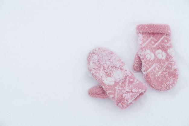 Zachte, warme, roze gebreide wanten op de witte sneeuw.