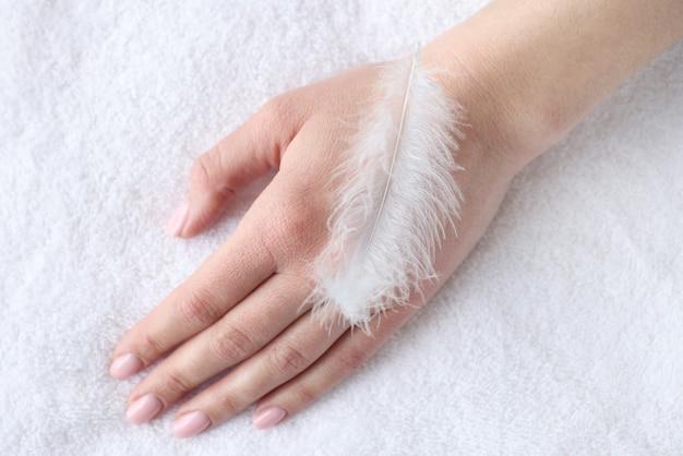 Zachte witte veer die op de close-up van de vrouwenhand ligt