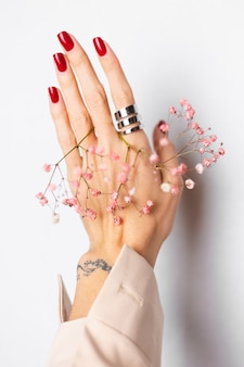 Zachte zachte foto van vrouwenhand met grote ring rode manicure houdt schattige kleine roze gedroogde bloemen op wit.