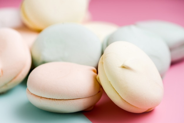 Zachte zephyr. detailopname. air marshmallows in pasteltinten op hemelsblauwe en roze achtergrond. plat liggen, close-up