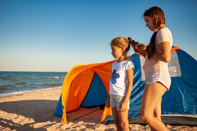 Zachte zorg voor geliefden en jongere meisjes aan de verlaten kust van de warme prachtige zee op een mooie avond