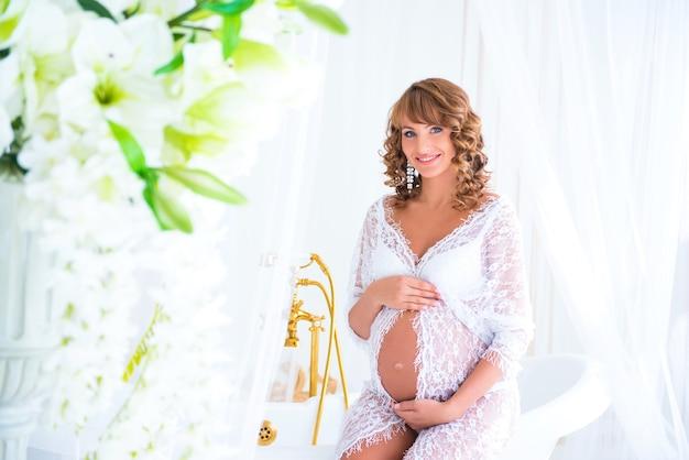 Zachte zwangerschap. aanstaande moeder in kanten jurk bij de vaas met bloemen
