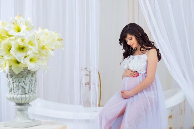 Zachte zwangerschap. mooi zwanger in lichte witte jurk met orchideeën.