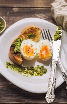 Zachtgekookt ei met geroosterd brood en pestosaus op rustieke houten achtergrond