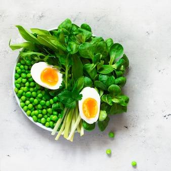 Zachtgekookte eieren met sla, daslook, doperwtjes en peterselie. gezond eten concept. wordt veganist