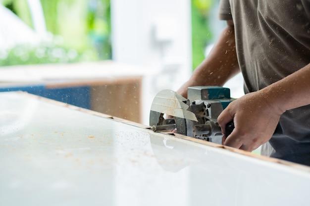 Zagen van hout voor de bouw, houtboor, timmerman, arbeider