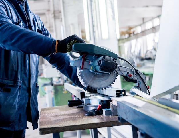 Zagen van pvc-profiel met cirkelzaag. industrieel materiaal. productie van pvc ramen en deuren.