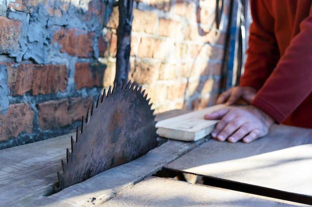 Zagerij. oude machine om planken te zagen. cirkelzagen. houtverwerkende industrie. een man houdt een plank vast en zaagt hem. timmerman die cirkelzaag gebruikt voor het snijden van houten planken.