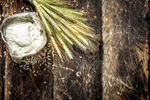 Zak met bloem en aartjes van tarwe op een houten achtergrond