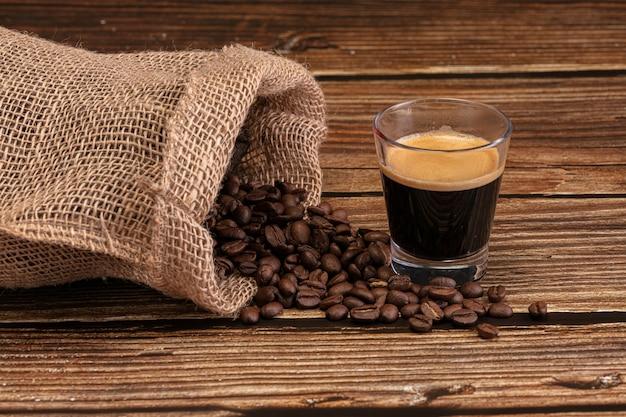 Zak met gebrande koffie met een kopje espresso koffie op een houten tafel