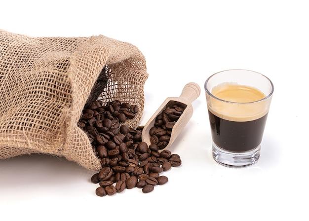 Zak met gebrande koffie met een kopje espresso koffie op wit