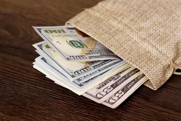 Zak met geld, dollars. dollar op een donkere houten achtergrond