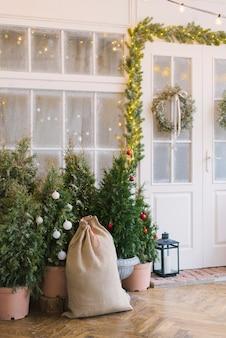 Zak met geschenken, kerstbomen bij de toegangsdeuren van een privéhuis versierd voor kerstmis