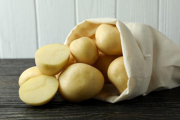 Zak met jonge aardappel op houten tafel