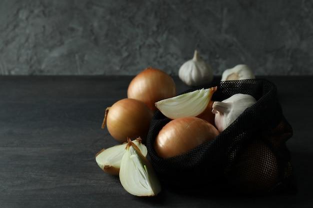 Zak met ui en knoflook op zwarte houten tafel