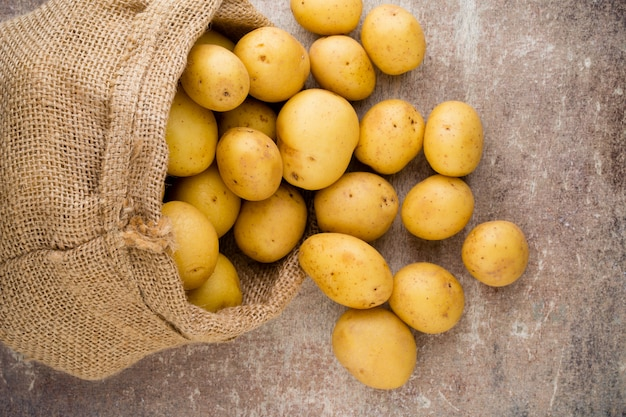 Zak met verse rauwe aardappelen op hout, bovenaanzicht.