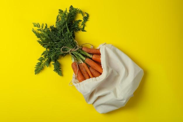 Zak met verse wortel op gele ondergrond