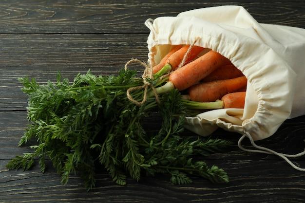 Zak met verse wortel op houten oppervlak