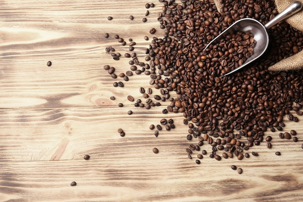 Zak, schep en koffiebonen op houten oppervlak