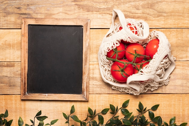 Zak tomaten naast leeg bord
