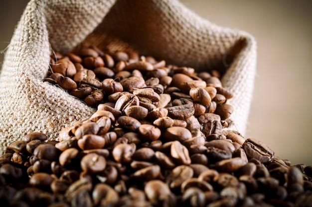 Zak van jute met koffiebonen wordt gevuld op houten achtergrond die.