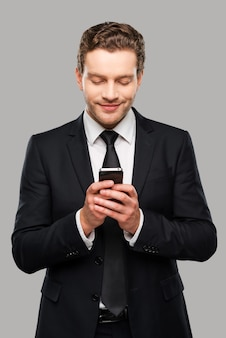 Zakelijk bericht aan het typen. zelfverzekerde jonge man in formalwear die mobiele telefoon vasthoudt en glimlacht terwijl hij tegen een grijze achtergrond staat