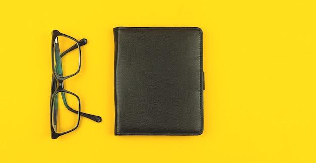 Zakelijk bureau met zwart lederen notitieblok en bril, bovenaanzicht, gele tafelachtergrond met kopieerruimtefoto
