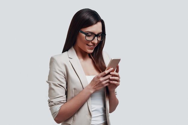 Zakelijk chatten. mooie jonge vrouw die naar een smartphone kijkt terwijl ze tegen een grijze achtergrond staat