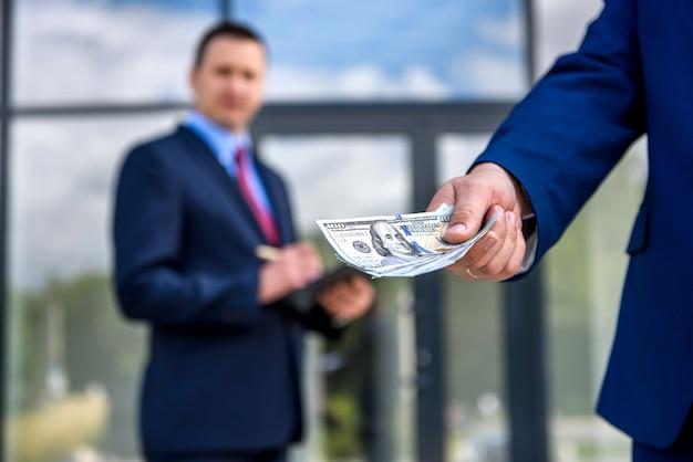 Zakelijk contract buitenshuis, partners met dollarbankbiljetten