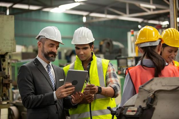 Zakelijk directeur en monteur ingenieur controleren en bespreken in fabriek