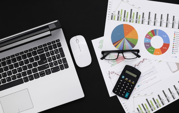 Zakelijk, economisch analyseonderwerp. werkruimte van econoom op een zwarte achtergrond. laptop, grafieken en grafieken met een rekenmachine. bovenaanzicht