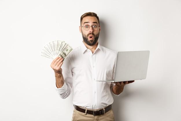 Zakelijk en e-commerce. man die verbaasd kijkt met geldinkomen, online werkt, laptop gebruikt, staande op een witte achtergrond