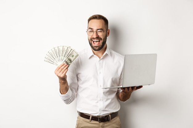Zakelijk en e-commerce. zelfverzekerde zakenman die laat zien hoe online werken, knipogen, geld aanhouden en laptop, staande op een witte achtergrond.