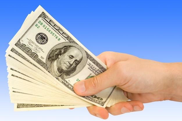 Zakelijk en financieel concept. geld in de hand over blauw