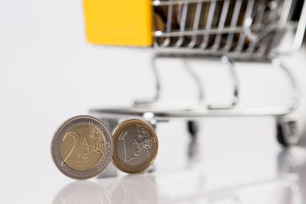 Zakelijk en financieel, shopping concept met winkelwagentje vol met meerdere munten op witte achtergrond