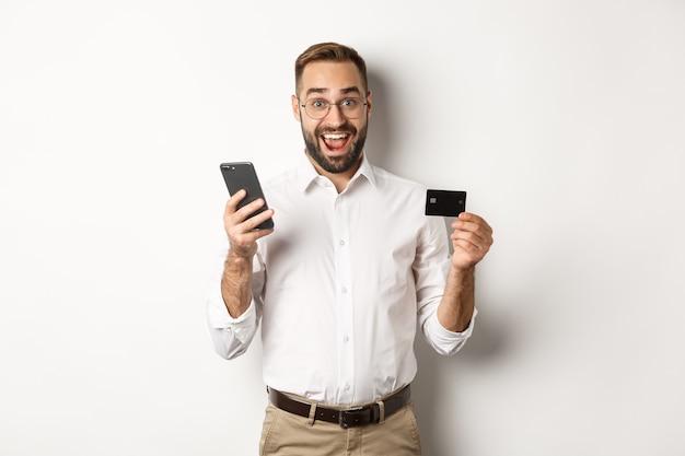 Zakelijk en online betalen. opgewonden man betalen met mobiele telefoon en creditcard, glimlachend verbaasd, staande op een witte achtergrond