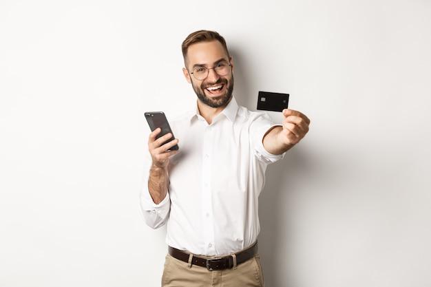 Zakelijk en online betalen. opgewonden man die zijn creditcard toont terwijl hij een smartphone vasthoudt, tevreden tegen een witte achtergrond