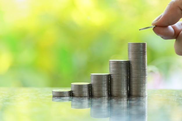 Zakelijk, geld, sparen en beveiligingsconcept. sluit omhoog van de holding van de mensenhand en zet een muntstuk bovenop stapel muntstukken met bokeh van de groene achtergrond van de bladaard en exemplaarruimte.