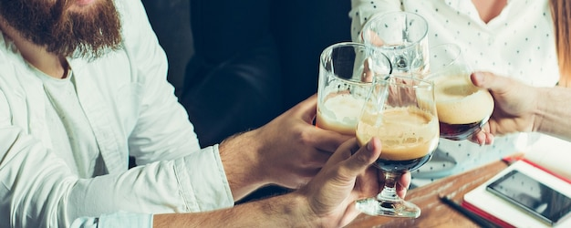 Zakelijk. handen van vrienden, collega's tijdens bier drinken, plezier maken, rammelende flessen, glazen samen.