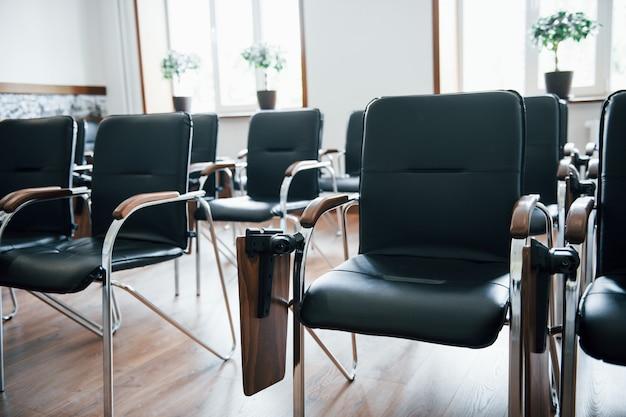 Zakelijk klaslokaal overdag met veel zwarte stoelen. klaar voor studenten