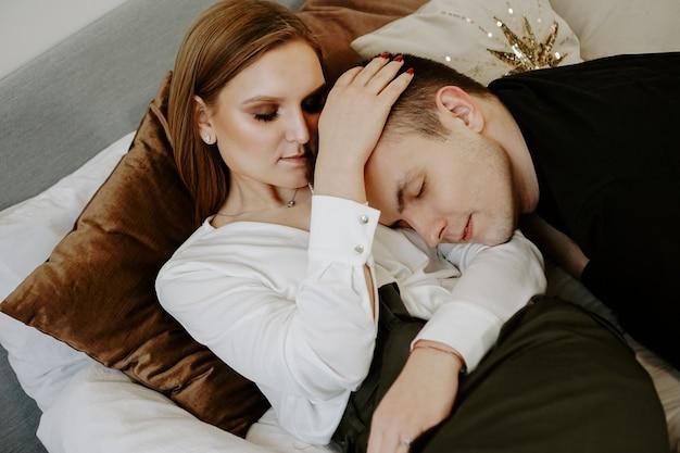 Zakelijk koppel op bed in hotelkamer - tedere knuffels