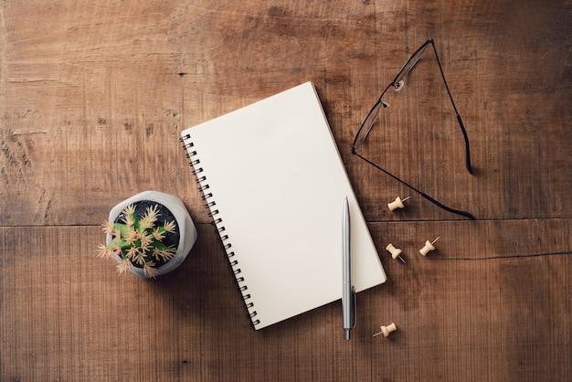 Zakelijk, onderwijs, stilleven, werk- of planningsconcept: bureautafel met open notitieboekje, pen en bril, plat leggen, mock-up