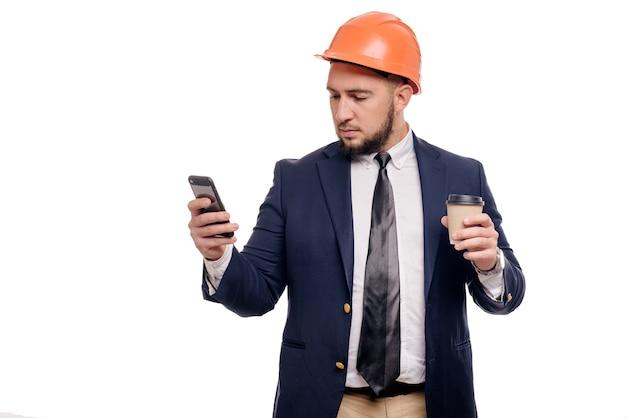 Zakelijk portret van verrast aannemer en ontwikkelaar, praten over telefoon. zakenman in harde hoed met kop koffie die zich over witte achtergrond bevindt. nieuws en koffieremconcept